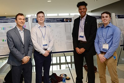 UML business analytics Asst. Prof. Asil Oztekin with three students who studied MLB statistics: Eric Rose, Joel Dabady and Mark Albee.