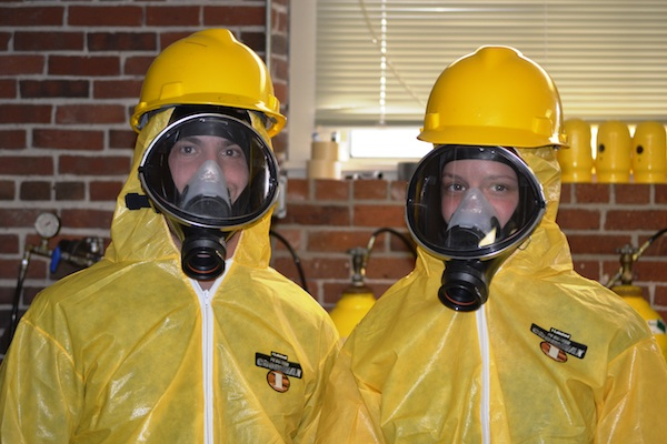 Students in the TNEC training program wear protective suits for cleaning up hazardous waste and materials.