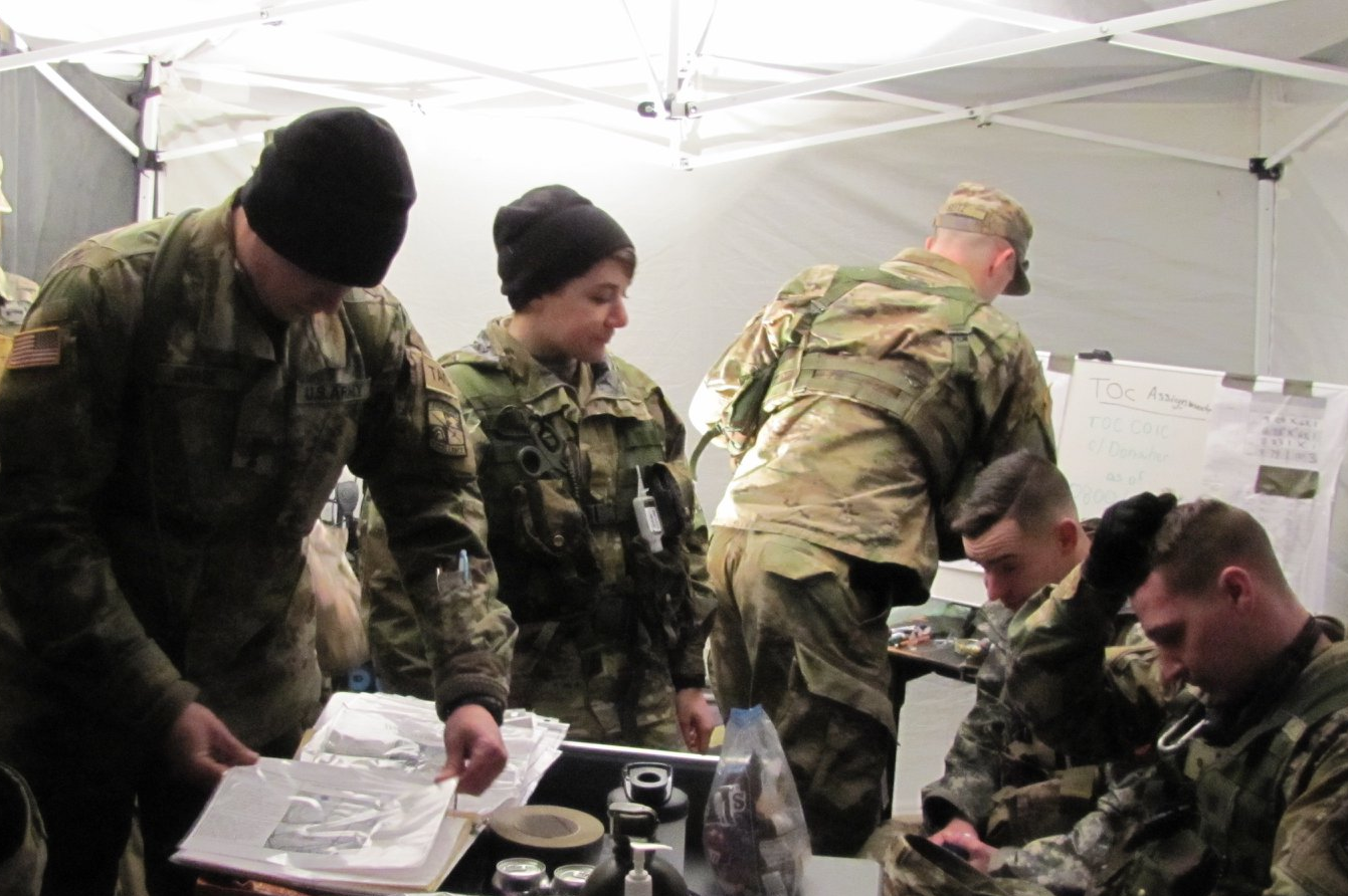 Cadets in a tent looking over documents