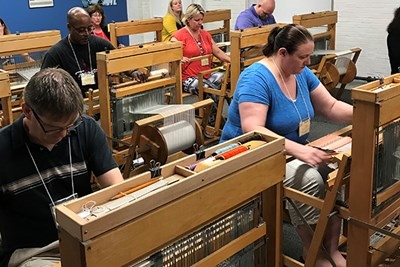 Teachers weave on manual looms at the Tsongas Industrial History Center in Lowell