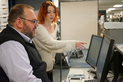 Brandi Zella, texttbooks manager at the River Hawk Shop, demos Follett Discover for Marshall Greenleaf, an adjunct professor