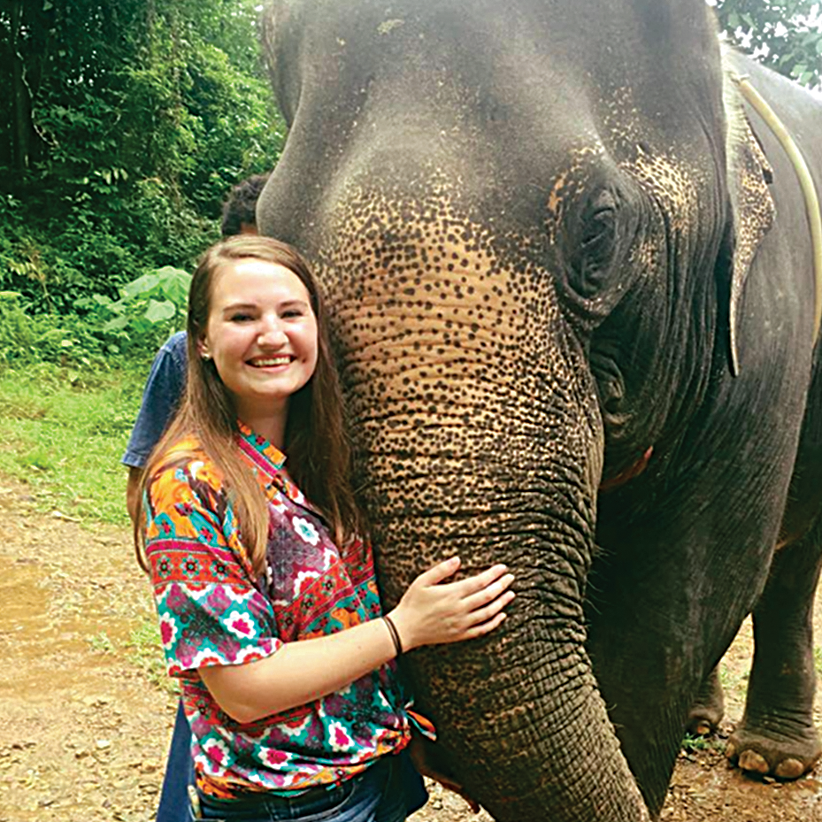 UMass Lowell student on study abroad program in Thailand next to an elephant.