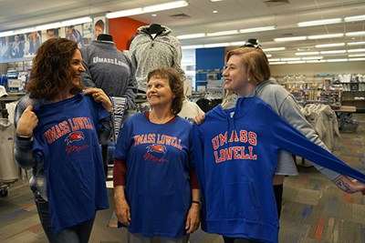 Deirdre Hutchison and Mary Humble check out UMass Lowell Mom shirts while Georgina Hutchison looks at a UMass Lowell shirt