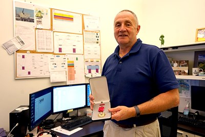Tim Corcoran holds his Legion of Merit award in his IT office