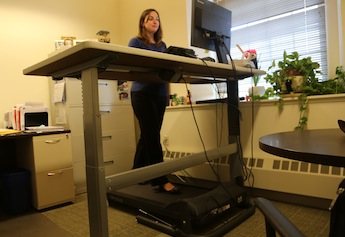 Hilary Clark is one of five employees testing the use of sit-to-stand desks and treadmills while working.