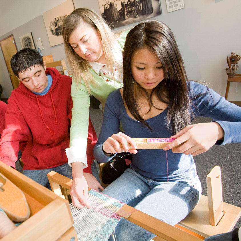 Teenagers and instructor at a loom learning how to weave at the Tsongas Industrial History Center