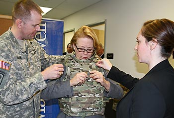 Maj. Joel Dillon and Deana Archambault of the U.S. Army's Natick Labs assist U.S. Rep. Niki Tsongas in trying on a lightweight body armor designed for women during the Feb. 7 launch of the HEROES initiative at UMass Lowell.