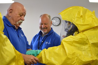 TNEC trainers help someone with their hazmat suit