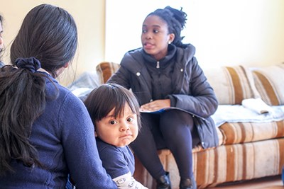 Ph.D. student Kelechi Adejumo explains the dangers of secondhand smoke to a family in the Healthy Homes project