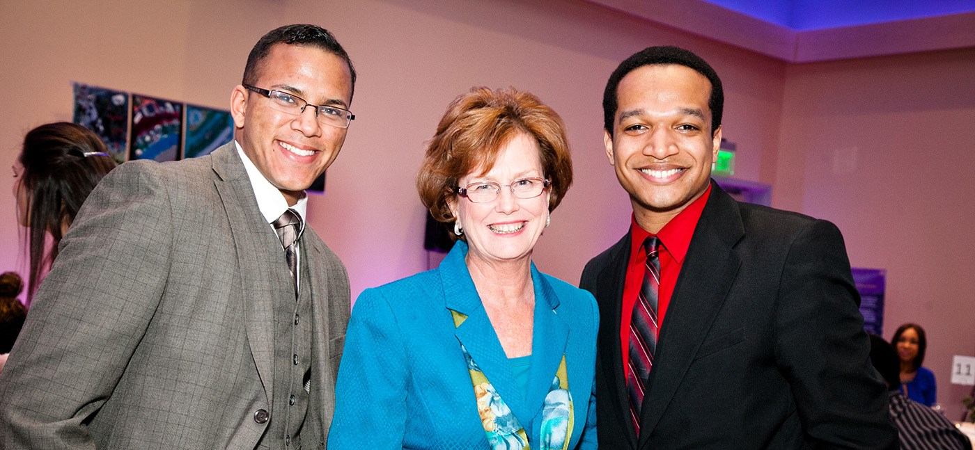 2 male students pose for a picture with Chancellor Jacquie Moloney at the 2015 MLK awards dinner.