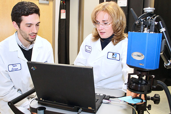 Physics doctoral student Tyler Iorizzo and Assoc. Prof. Anna Yaroslavsky operate the optical polarization imager (OPI) at the university's Advanced Biophotonics Laboratory.