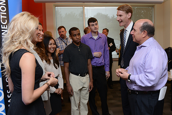 Kronos CEO Aron Ain, right, and Francis College of Engineering Dean Joseph Hartman, second right, congratulate the university's first cohort of co-op students at the Chelmsford-based software company.