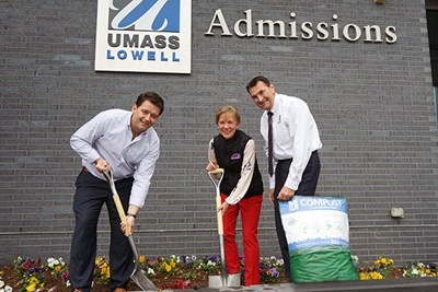 University staff members pose with a bag of the new compost