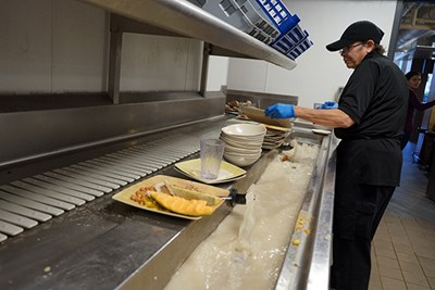 A dining hall employee removes food waste to be composted