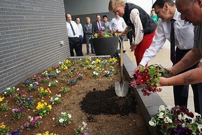 Joanne Yestramski helps plant flowers with the compost