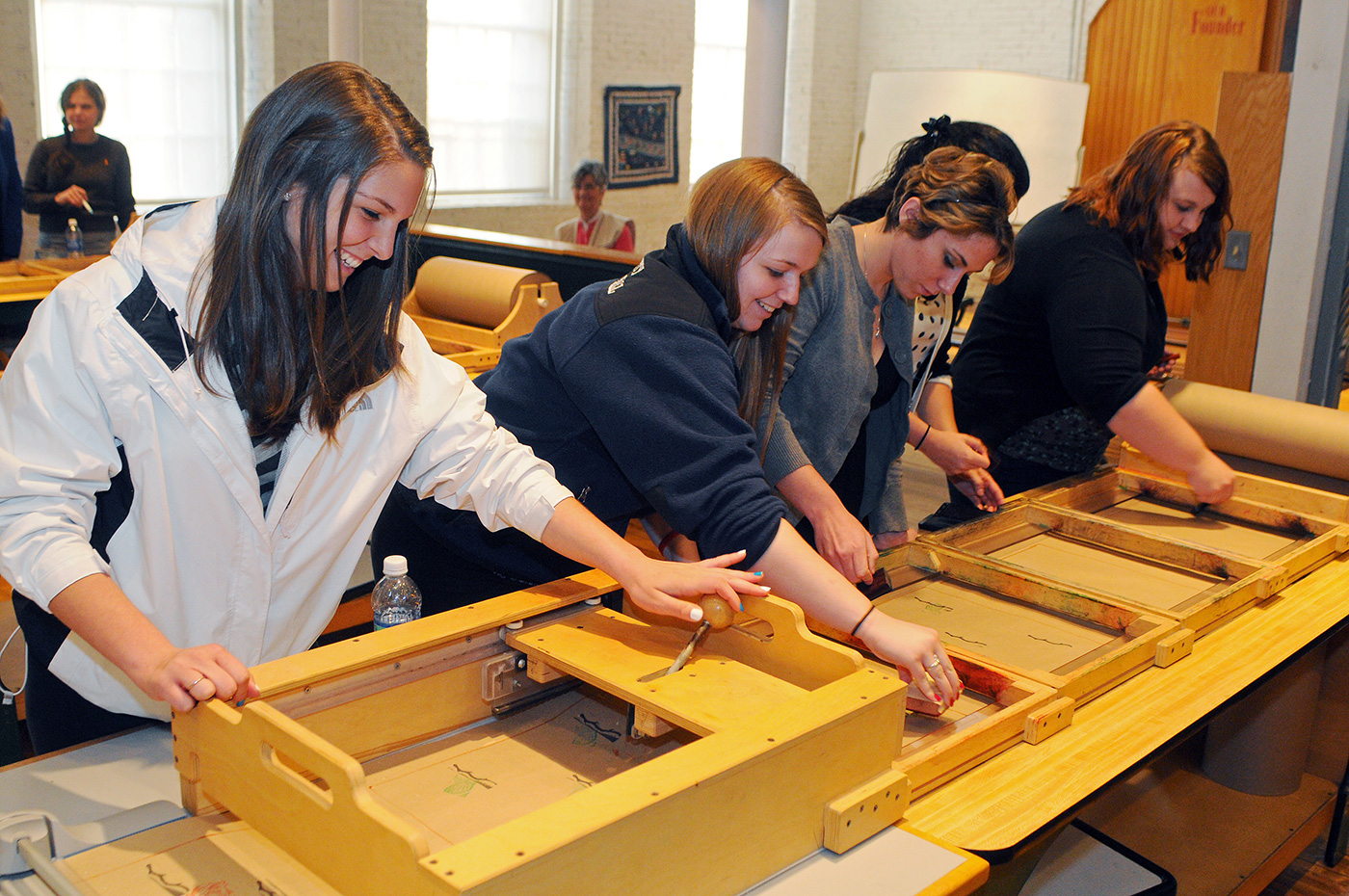 Smiling students use museum equipment to practice mass printing techniques