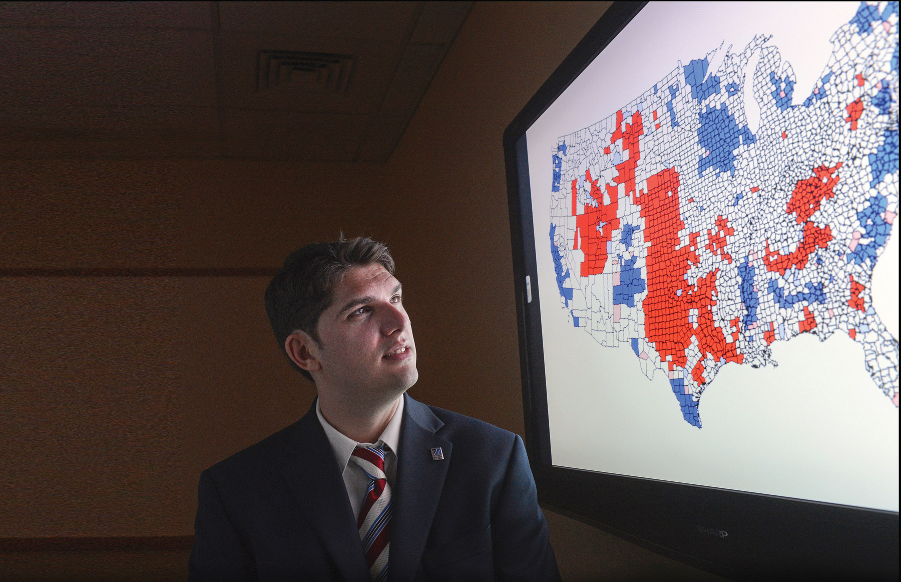 Prof. Joshua Dyck looks at polling map on large screen