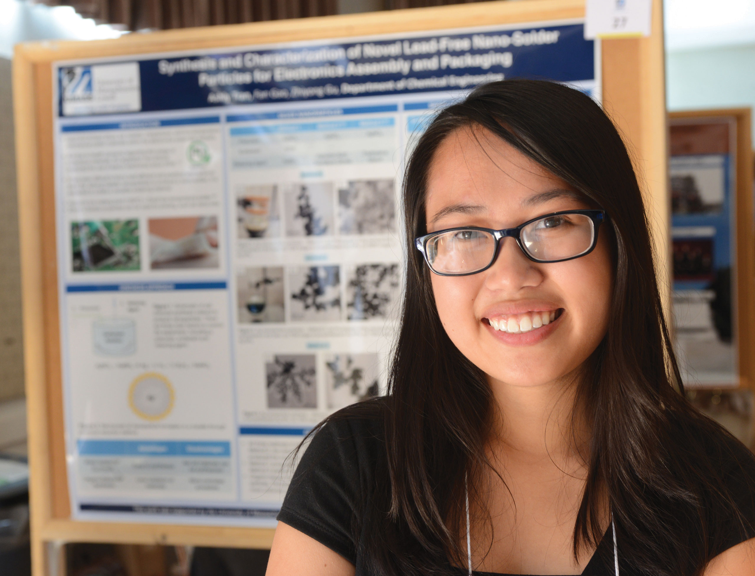 UMass Lowell Co-op Scholar Ashly Tran standing in front of research poster