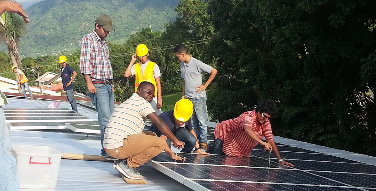 UMass Lowell students and Loyola Electrical Students installing PV modules on a roof in a developing country.