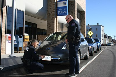 UML police officers affix a license plate to their new electric vehicle