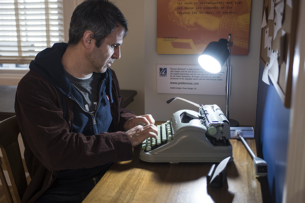 Jack Kerouac Writer-in-Residence Steve Almond tries out a typewriter in the Kerouac Retrieved exhibit at Allen House.