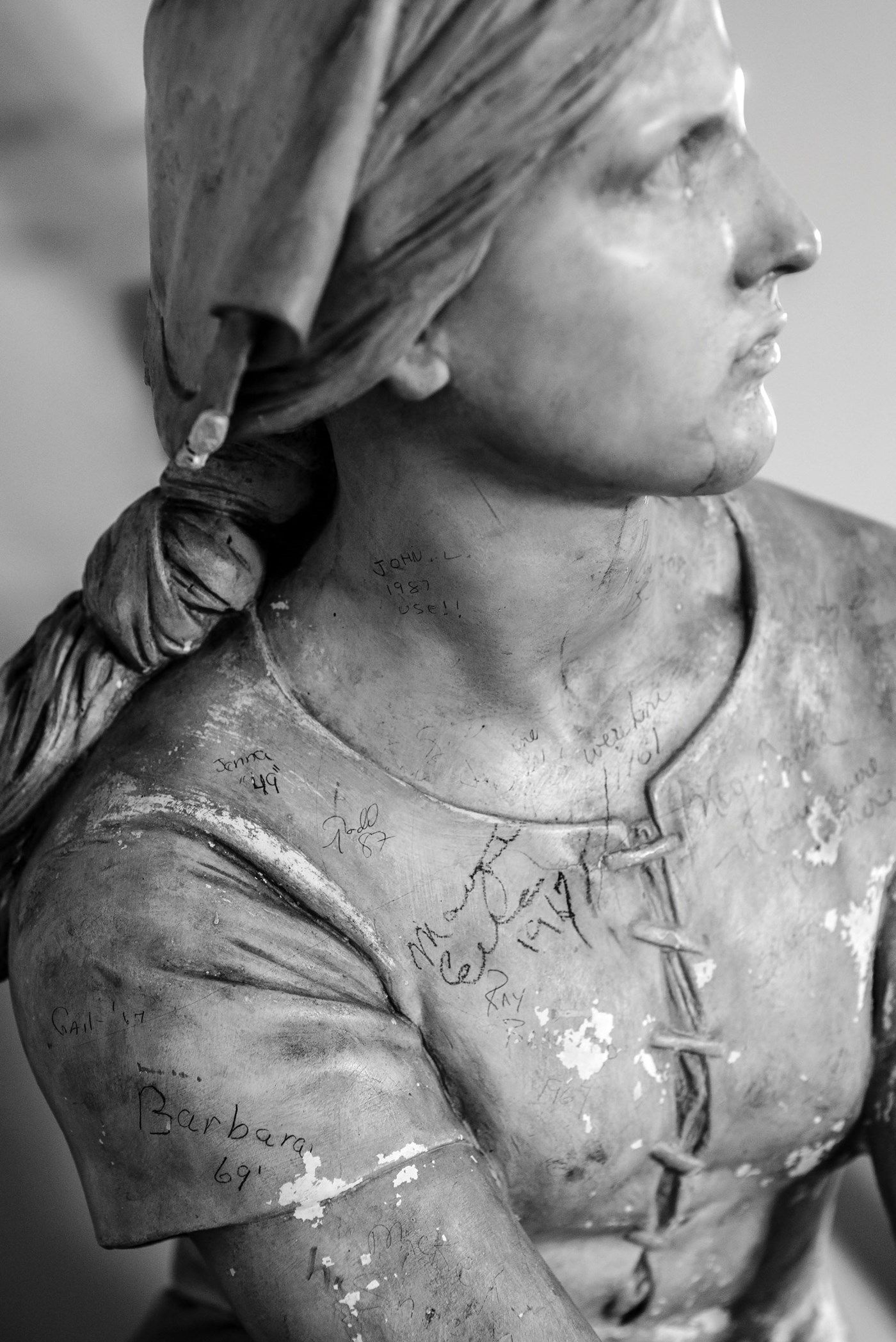 Plaster sculpture of Joan of Arc adorned with student signatures