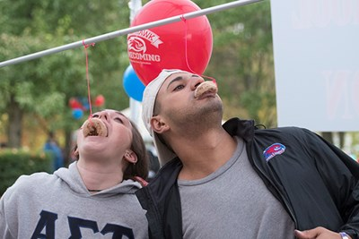 Students eat donuts hanging from strings at UML Homecoming