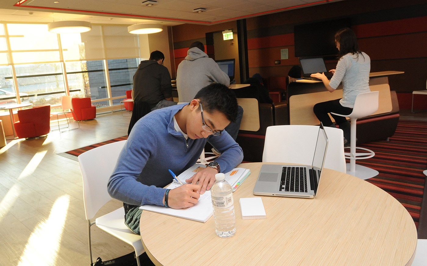 Umass Lowell students in University Suites building, studying and doing homework in the common room.