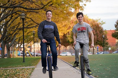 Evan Jones and Andrew Terrill ride their unicycles on East Campus