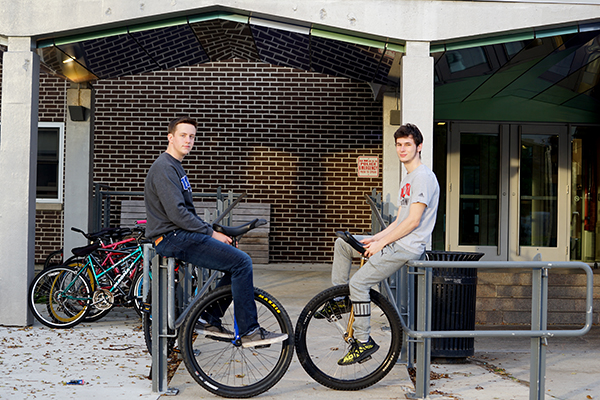 Evan Jones and Andrew Terrill with their unicycles outside of Leitch Hall