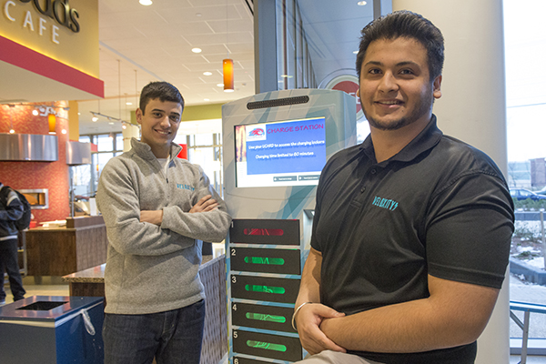 Seniors Felipe Nascimento, left, and Upkar Singh are happy to see their company's cell phone charging kiosk being used at University Crossing. Photo by Tory Germann.