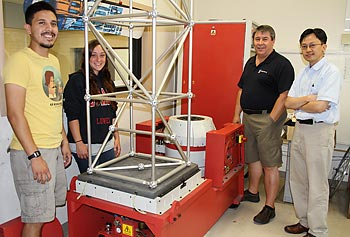 Prof. Peter Avitabile, second from right, shows the vibration shaker system to, from left, mechanical engineering graduate students Jesus Reyes and Julie Harvie and civil engineering Asst. Prof. Tzu-Yang Yu.