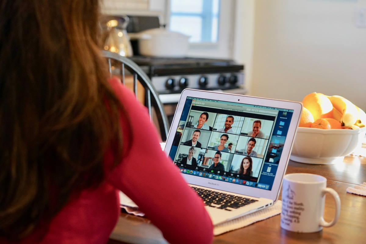 Stock Image: Woman sitting at desk with laptop computer in front of her with video conference showing 9 people on screen.