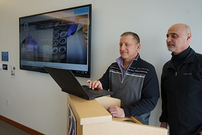 Information Technology staff members try the wireless presentation technology in a University Crossing conference room