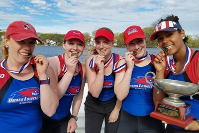 The women's varsity four rowers celebrate with their gold medals