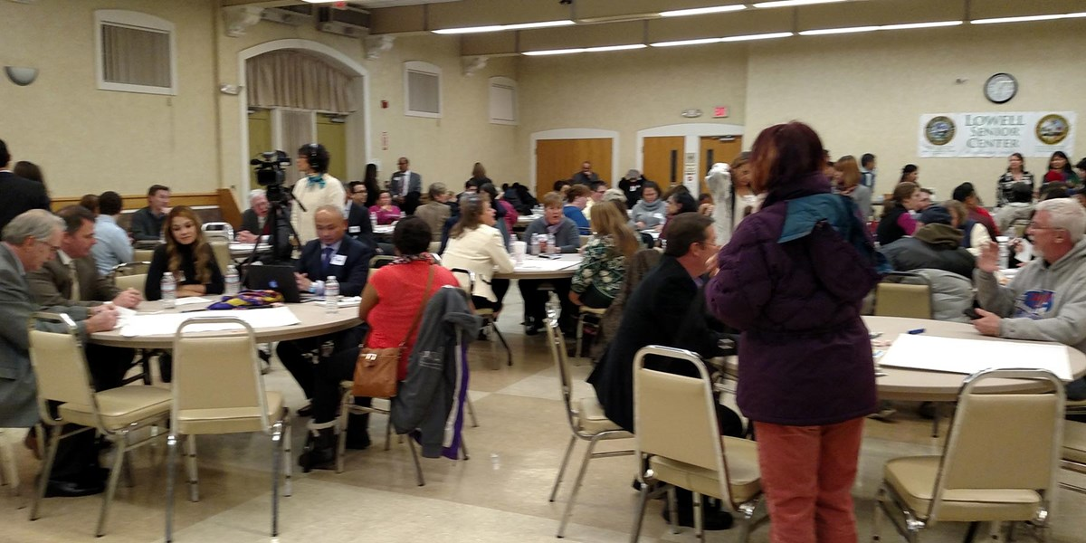People seated at round tables talking at the Lowell Senior Center