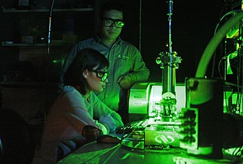 Assoc. Prof. Xuejun Lu, standing, works with his graduate student on a high-powered laser in the lab.