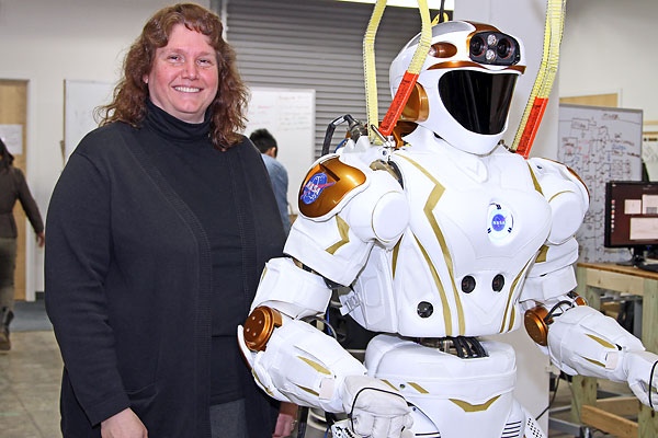 Prof. Holly Yanco poses with Valkyrie at the university's New England Robotics Validation and Experimentation (NERVE) Center.