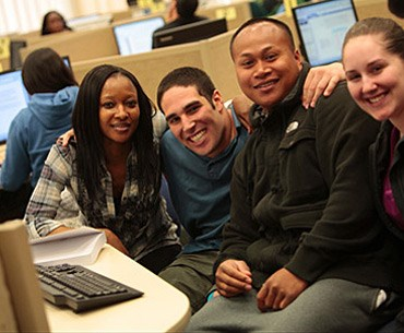 Four students posing together while using a computer in the computer room.