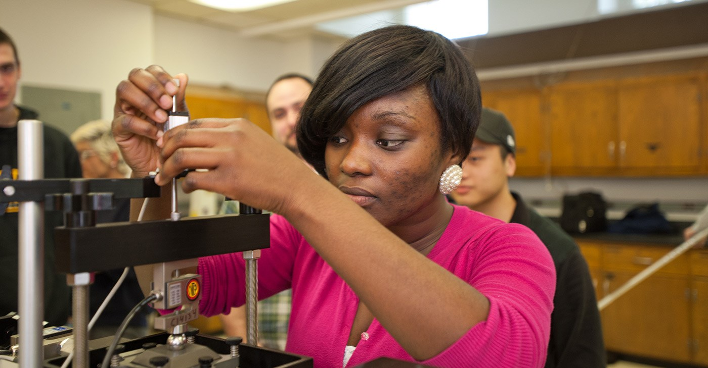 A Female African American UMass Lowell student working in a Civil & Environmental Engineering lab.