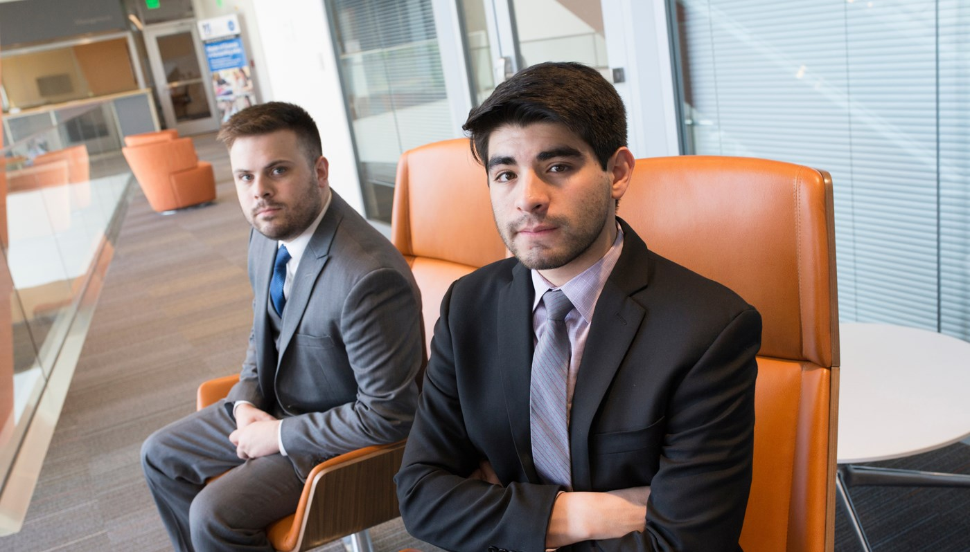 Alejandro Lopez pictured in a suit sitting with another UMass Lowell student, both sitting in the Pulichino Tong Building in orange chairs looking at the camera
