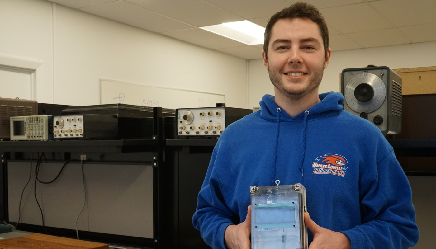 Electrical Engineering major Alex DiBuono poses with the IV Alert system, a prototype device that monitors the amount of fluid in an infusion bag and is connected to software at the nursing station