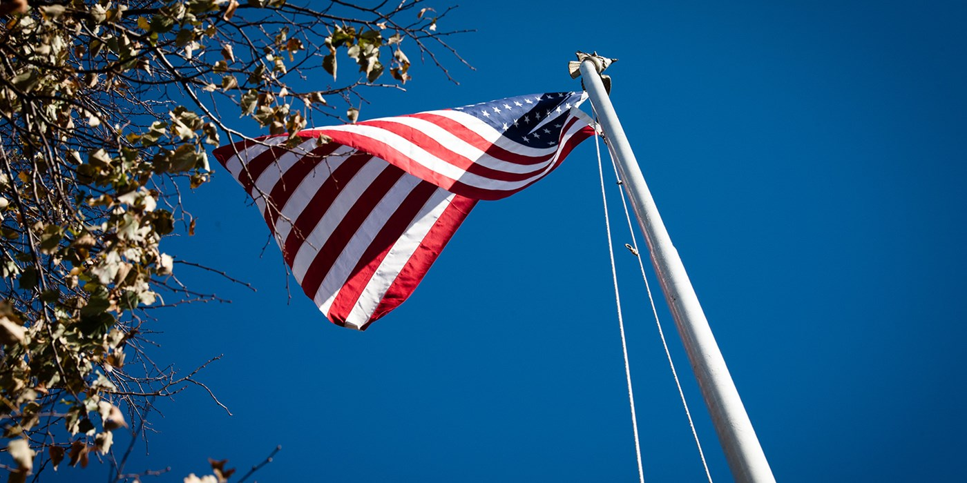 An American flag waving in the wind as seen from below.