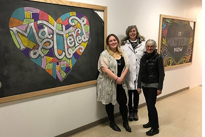 Chalk artist Anna Dugan '18, Assoc. Prof. Marie Frank and Art & Design Chair Jehanne-Marie Gavarini between the designs Dugan added to the historic chalk boards found during the renovation of Coburn Hall.
