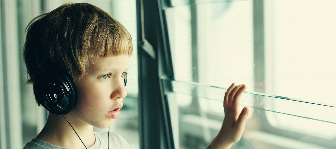 Young boy wearing headphones and staring out the window at the airport.