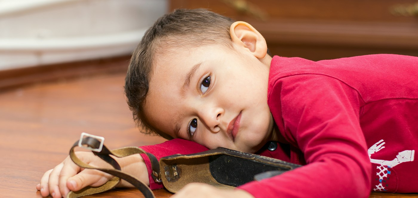 Little boy playing with a binocular case, lying on the floor looking at the camera.