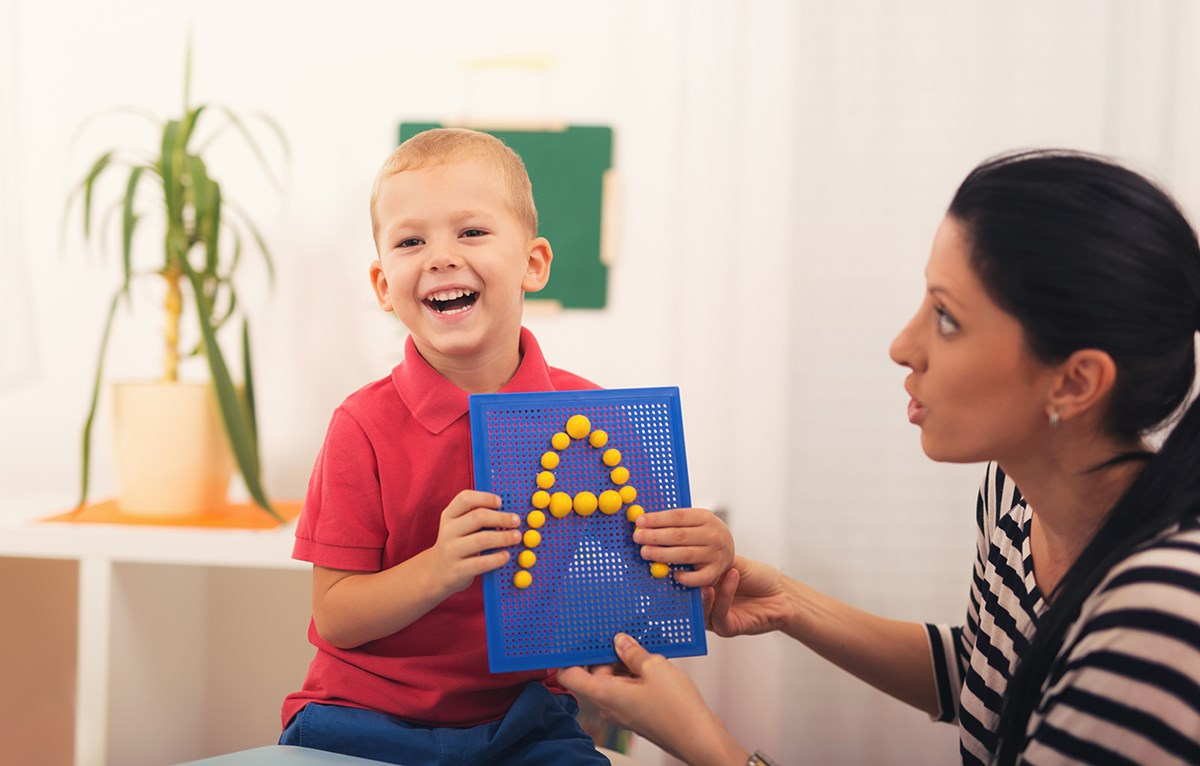 "Little boy smiling and holding up letter ""A"" with female speech therapist."