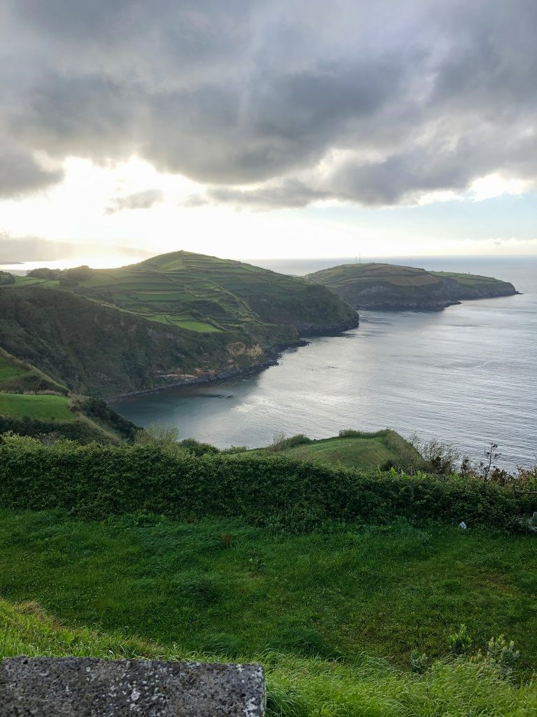 A beautiful, green hilly landscape touching the sea at sunset in Azores