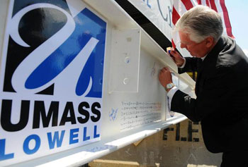 Chancellor Meehan signs the beam.