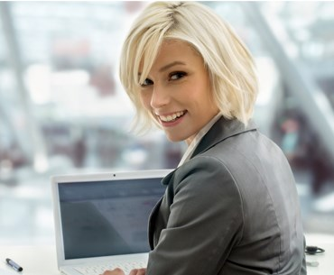 A professionally dressed blonde women working on the computer.